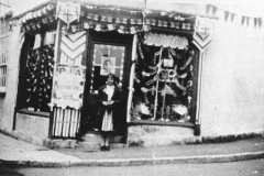 002810 Jim Southwood Saddlers and harness makers shop decorated for the Coronation and the youngest daughter standing in the doorway 1937